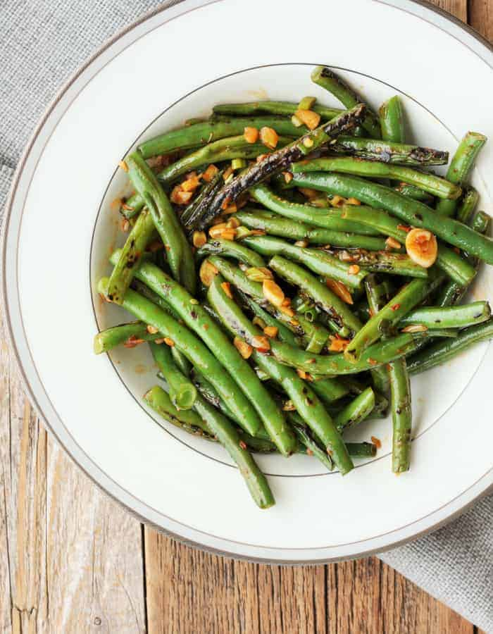 a round white plate full of spicy green beans