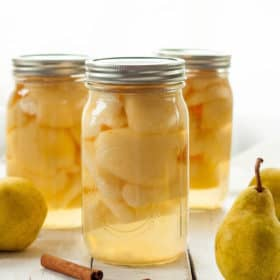 Three jars of canned pears on a wooden board with fresh pears and cinnamon sticks