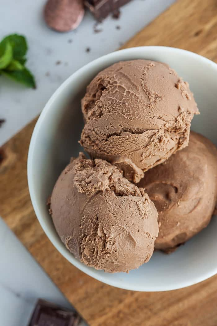 3 scoops of chocolate vegan ice cream in a white bowl