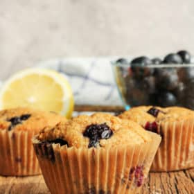 Three whole wheat blueberry muffins on a wooden board with a lemon and a bowl of blueberries