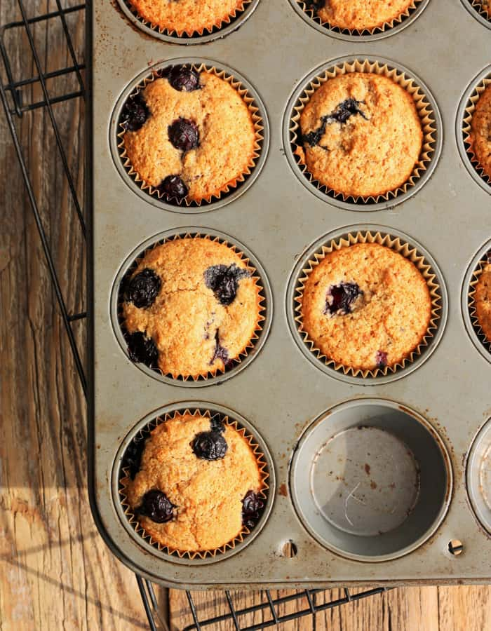 A muffin tin full of whole wheat blueberry muffins