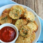 fried zucchini chips on a white plate with marinara