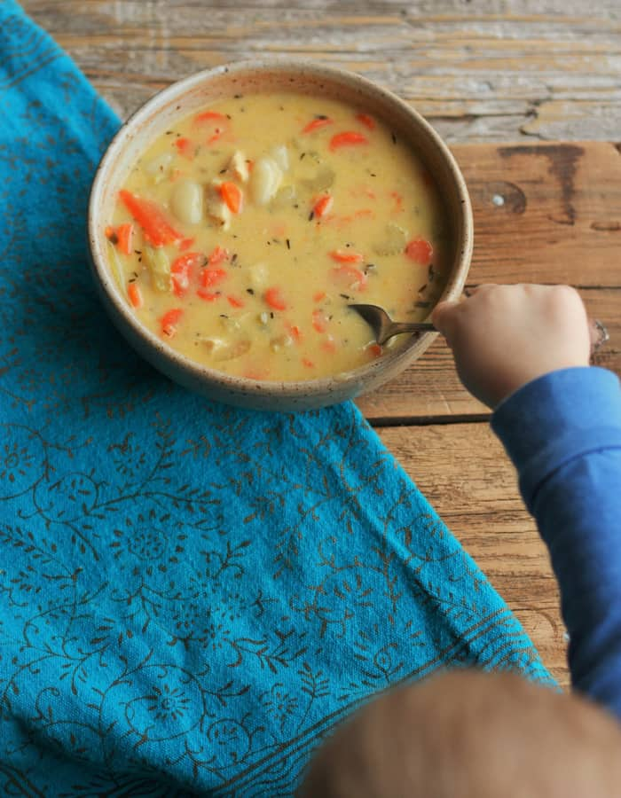 A toddler taking a spoonful of chicken gnocchi soup
