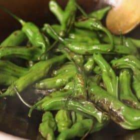 blistered shishito peppers in a wok | sustainablecooks.com
