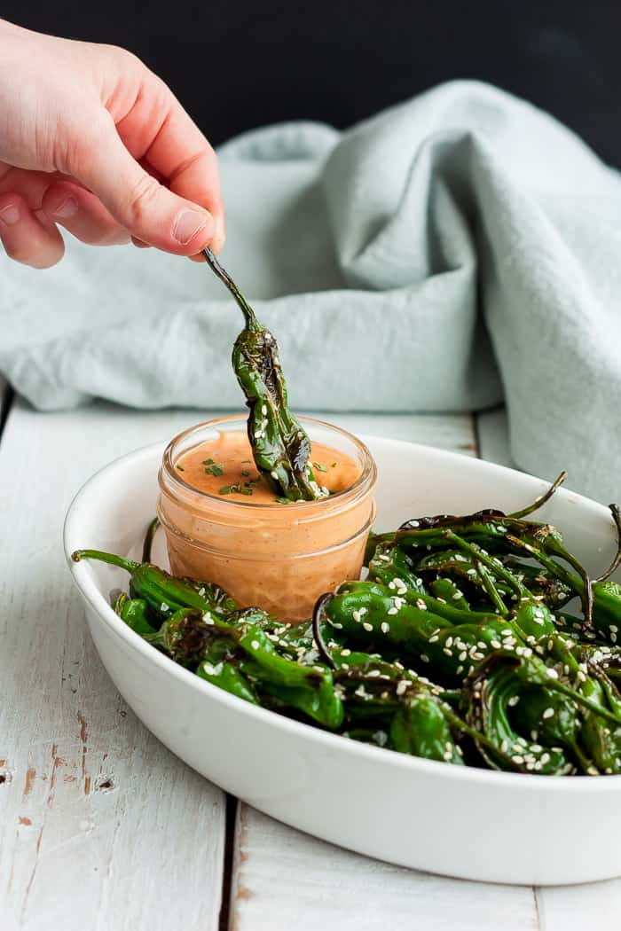 a blistered shishito pepper dipping a pardon pepper into a spicy dipping sauce
