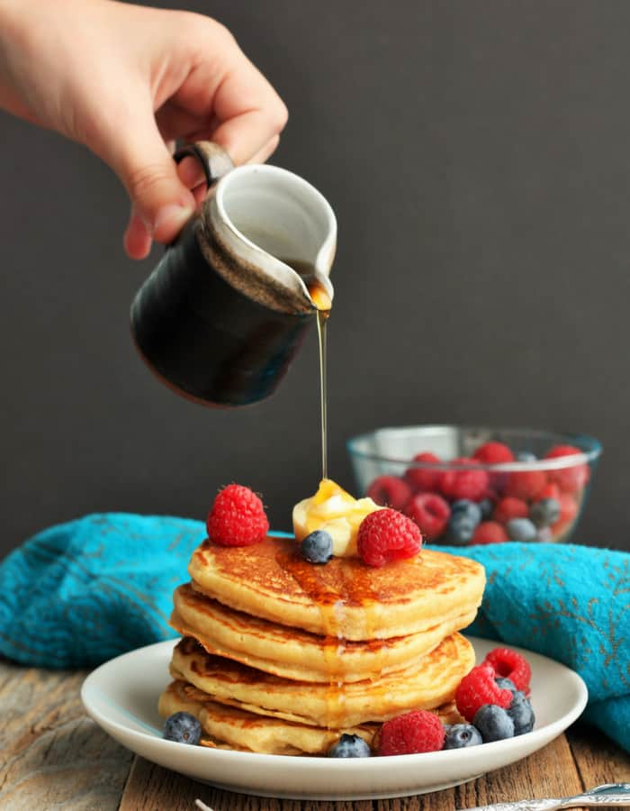 A hand pouring syrup on a stack of whole wheat pancakes
