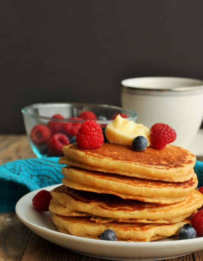 A stack of whole wheat pancakes topped with fruit and a mug of coffee in the background