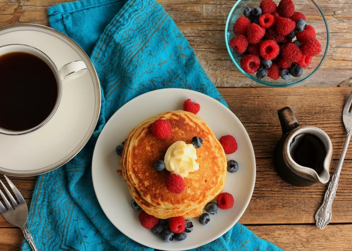 A plate with whole wheat pancakes with butter and berries with a mug of coffee and a bowl of fruit
