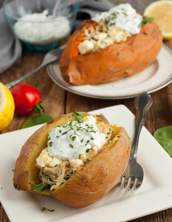 two instant pot stuffed sweet potatoes on plates with tomatoes and spinach