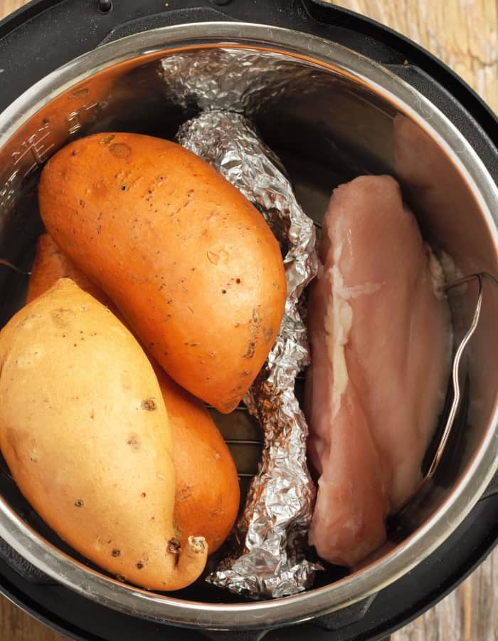 An instant pot with sweet potatoes and chicken breast