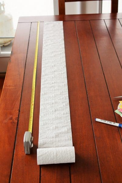 a roll of toilet paper and a measuring tape on a wooden table