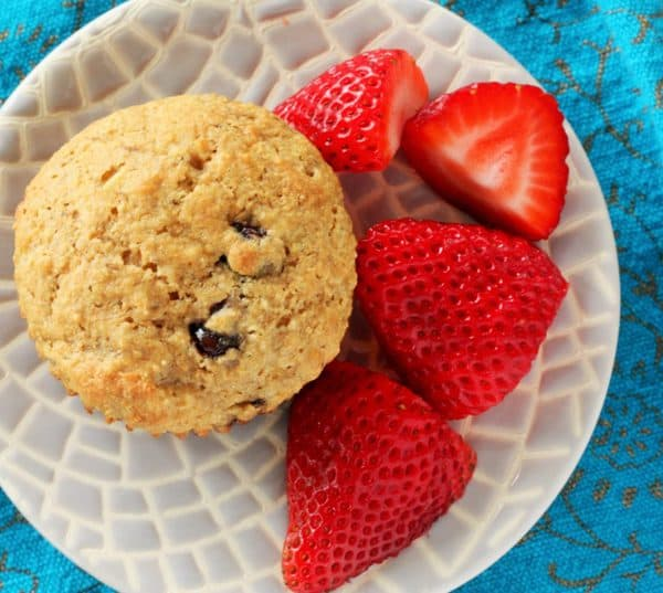 whole wheat banana chocolate chip muffins and strawberries on a plate on a blue cloth