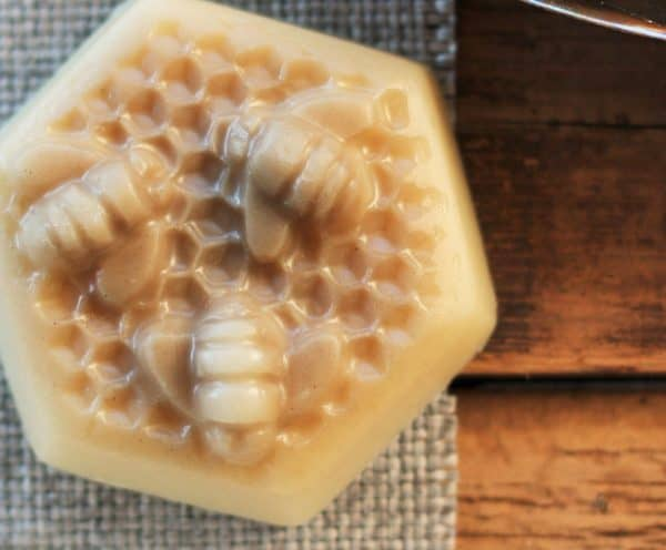 homemade hard lotion bar with a bee design sitting on burlap on a wooden background