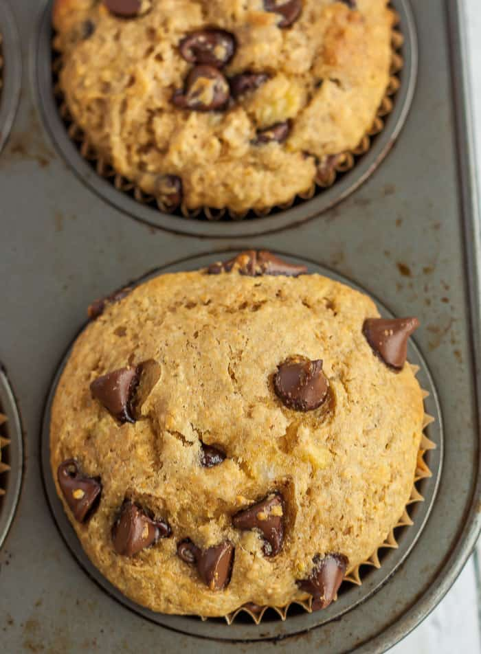an upclose image of a banana muffin with chocolate chips in a muffin tin