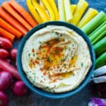 a rainbow of veggies with a bowl of garlic hummus recipe in the middle