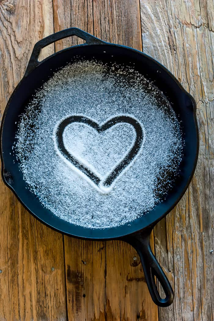 a cast iron skillet with a heart drawn in salt