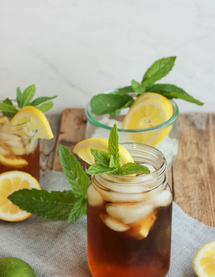 Glasses of healthy sweet tea with lemon and mint on a wooden board