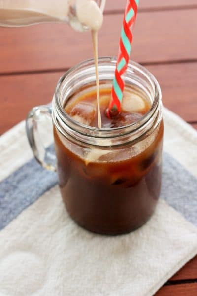a glass of cold brew coffee sitting on a white and blue cloth with coffee cream being poured