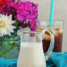 sugar-free coffee creamer in a glass pitcher with flowers and ice coffee