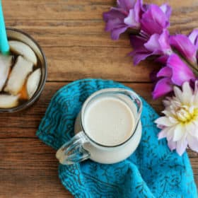 sugar-free coffee creamer in a pitcher on a blue cloth with flowers and iced coffee