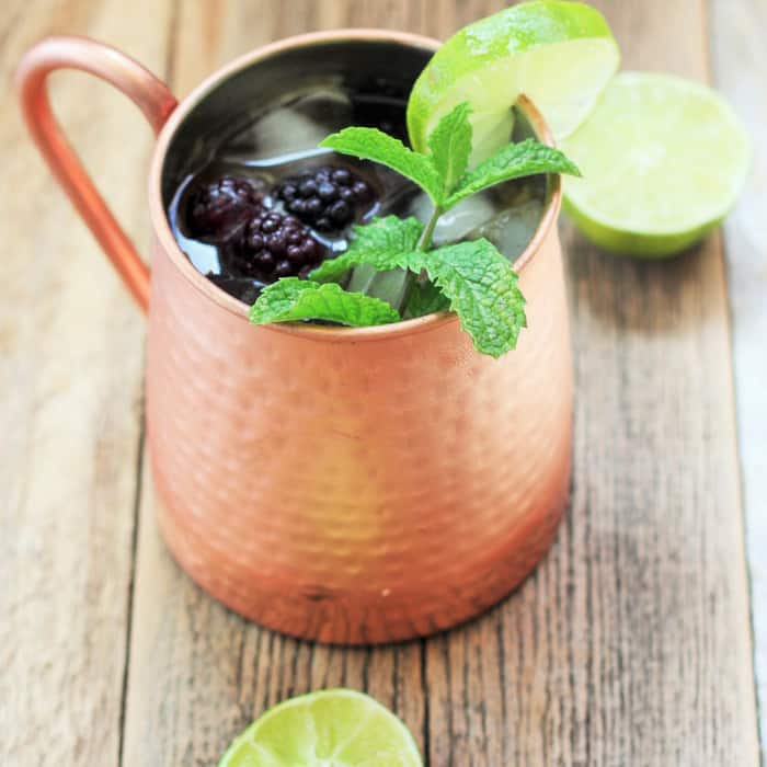 a blackberry and peach moscow mule in a copper mug with mint and lime on a wooden board