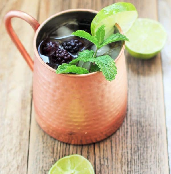 moscow mule with mint and lime in a copper mug on a wooden board