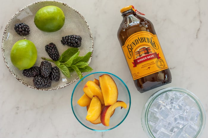 blackberries, limes, mint, peaches, and ginger beer for making a peach moscow mule