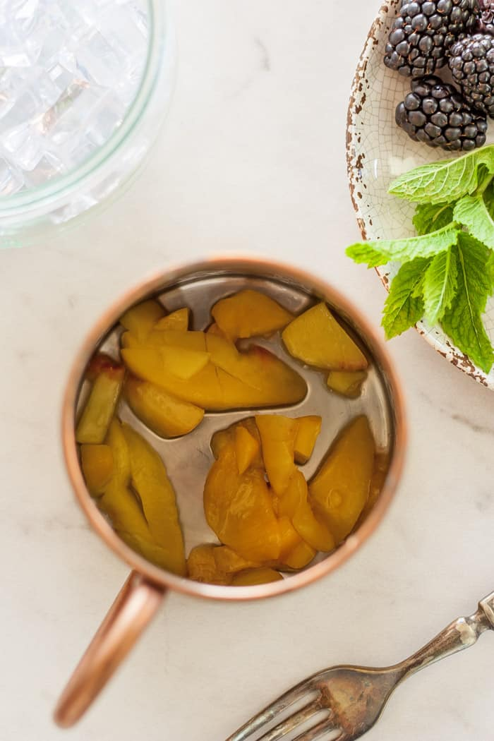 Peaches in the bottom of a copper mule mug