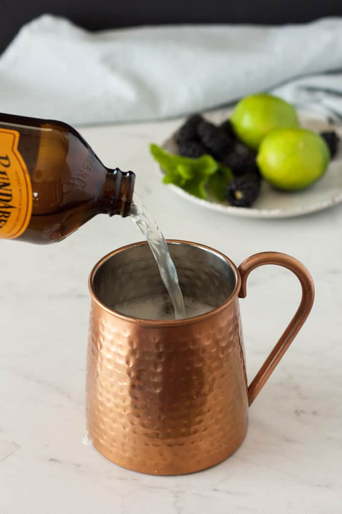 a bottle of ginger beer being poured into a copper mug