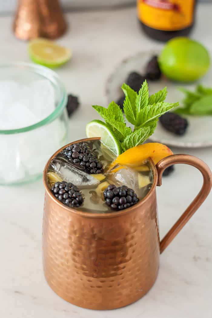 a peach moscow mule with blackberries and mint on a white background