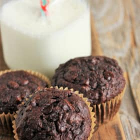 three double-chocolate zucchini muffins and a glass of milk with a straw on a wooden board