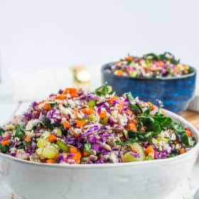 a white and blue bowl full of kale chopped salad