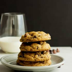 four whole wheat chocolate chip cookies on a plate with a glass of milk