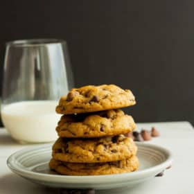 A stack of whole wheat chocolate chip cookies on a plate with a glass of milk
