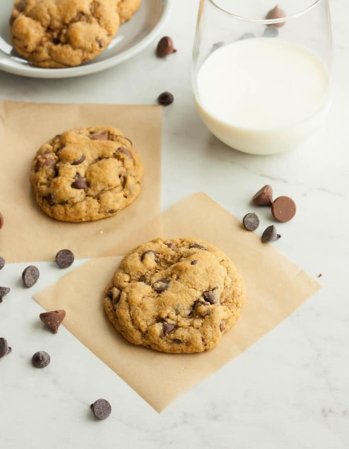 two whole wheat chocolate chip cookies on parchment with milk