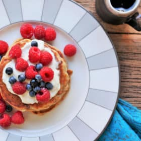 apple pie pancakes on a plate topped with berries and greek yogurt