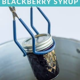 canning tongs putting a jar of blackberry syrup in a canner