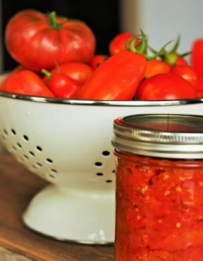 A jar of homecanned whole tomatoes in front of a strainer of tomatoes