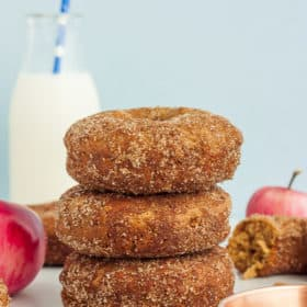 3 cinnamon apple donuts stacked up with apples and a bottle of milk