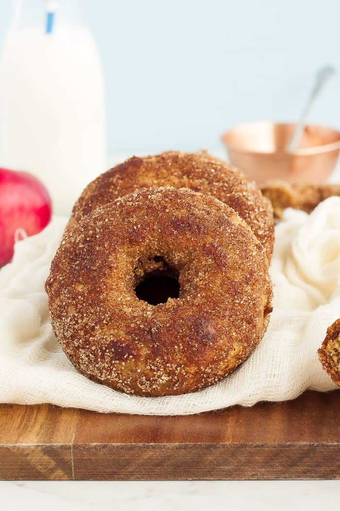 cinnamon apple donuts on a wooden board with apples and milk