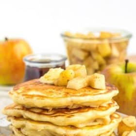 an overhead photo of apple pancakes on a plate with butter and diced apples