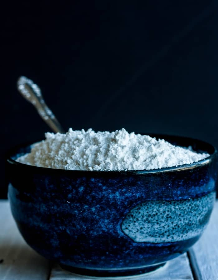 homemade powdered sugar in a blue bowl with a black background