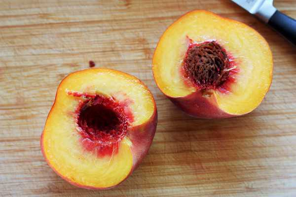 a peach split in half on a cutting board with a paring knife