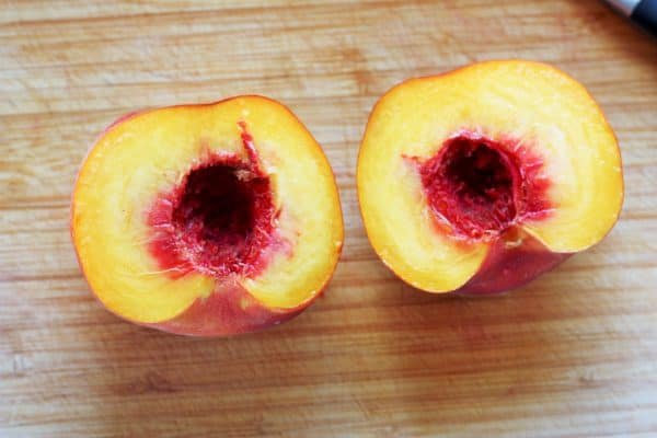 a peach split in half on a cutting board with the pit removed