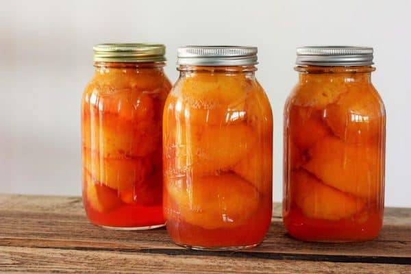 three canning jars full of canned peaches