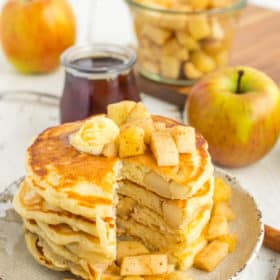 A stack of healthy apple pie pancakes with a slice cut out