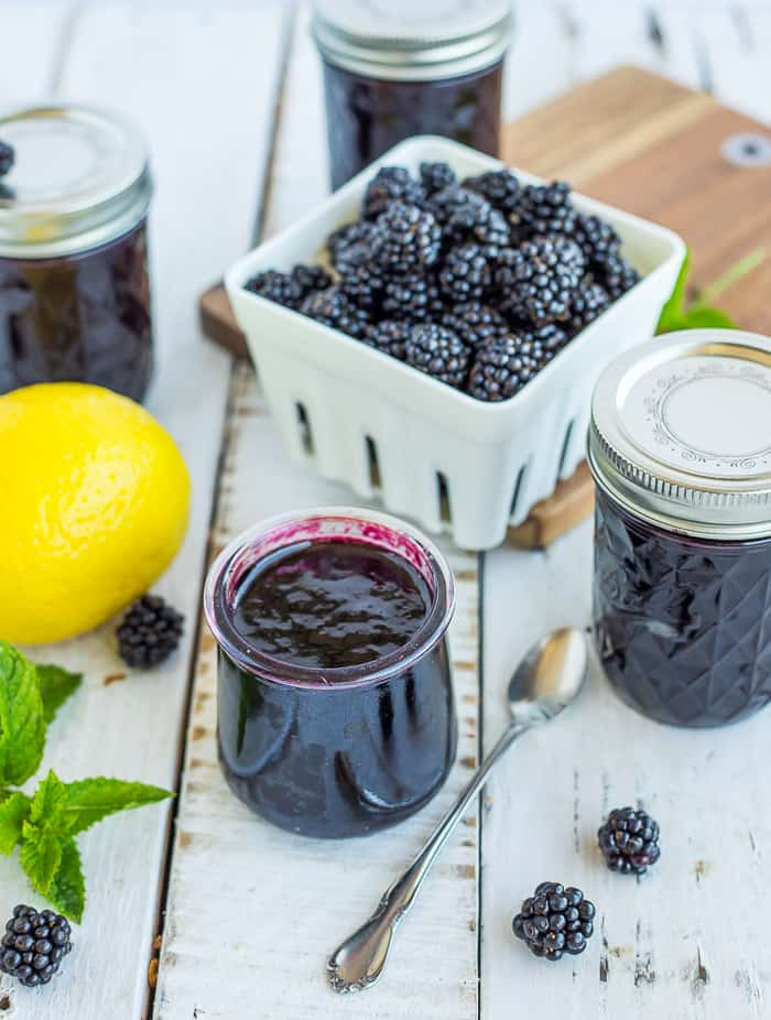 a small jar of blackberry pancake with a lemon and mint on a white board
