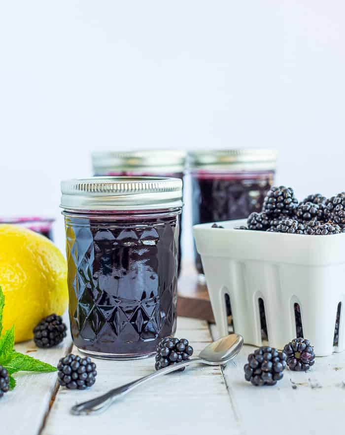 jars of blackberry syrup and a basket of blackberries on a white board