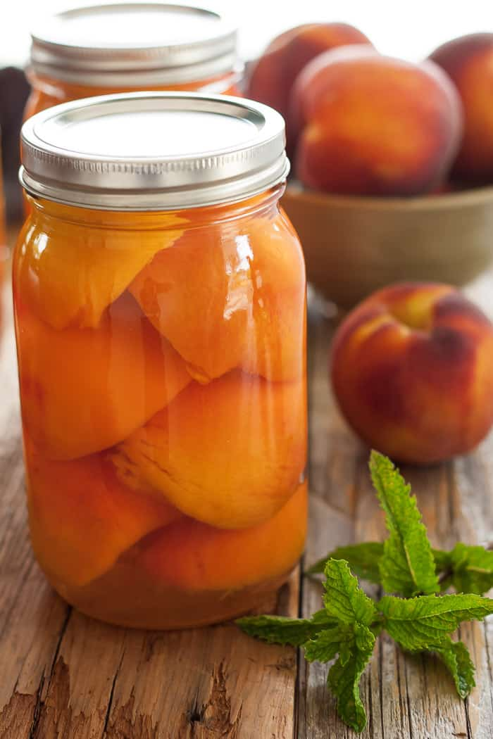 a jar of canned peaches with fresh peaches and mint