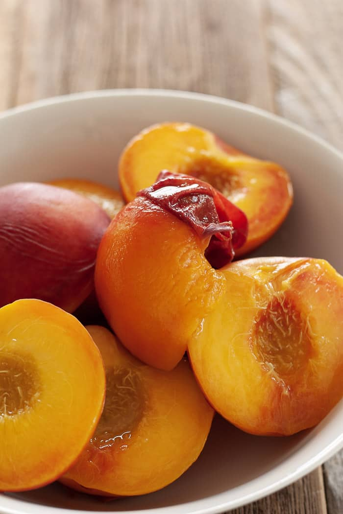 a bowl of peaches with the skins peeling off